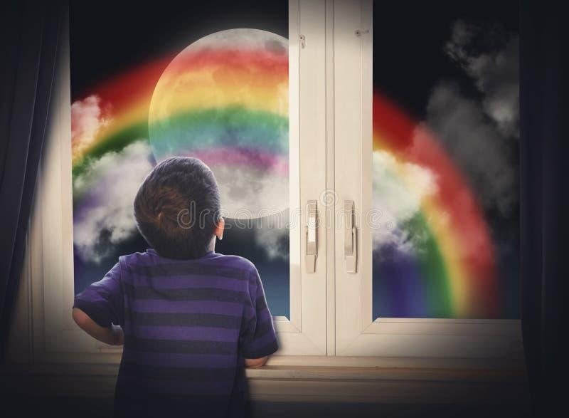 看彩虹月亮的男孩在晚上 免版税库存图片