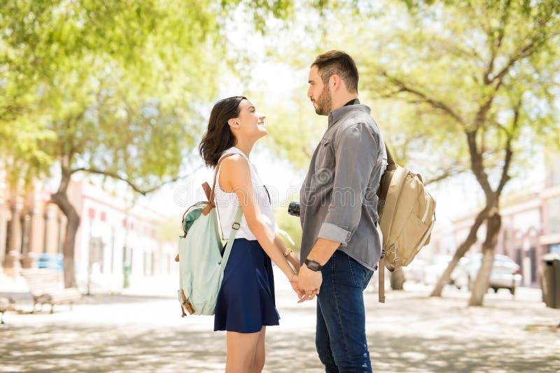 看彼此和握手的年轻愉快的夫妇 库存图片