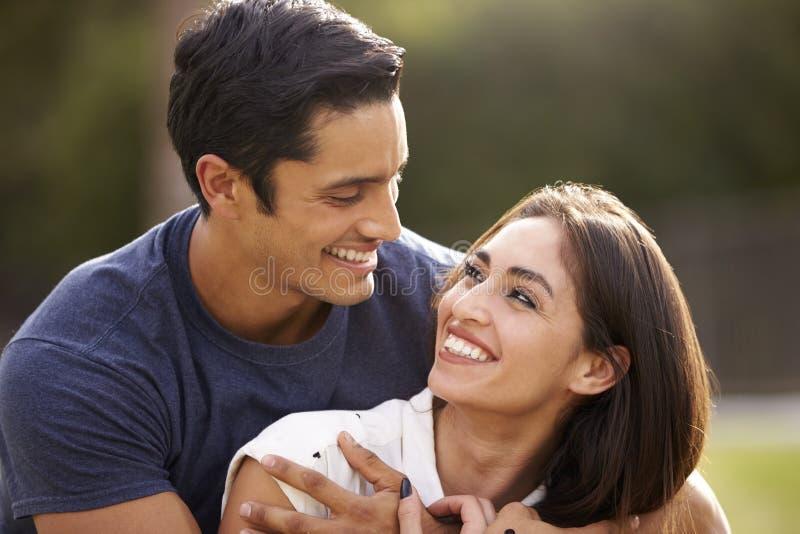 看彼此微笑,关闭的年轻西班牙夫妇  免版税库存图片