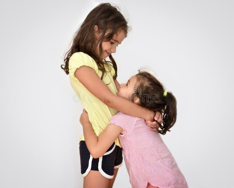 看彼此的两个拥抱的姐妹 库存照片