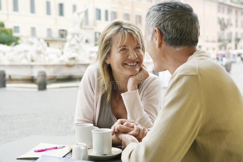 看彼此的夫妇室外咖啡馆 库存图片