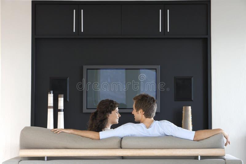看彼此的夫妇,当放松在长沙发时 免版税库存照片