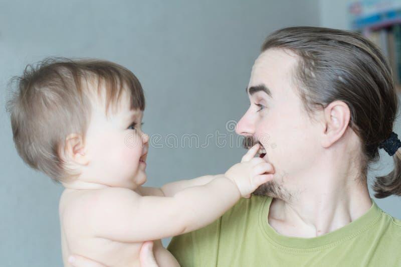 看彼此的愉快的微笑的父亲和小女儿 在简单的生活方式的幸福 免版税图库摄影