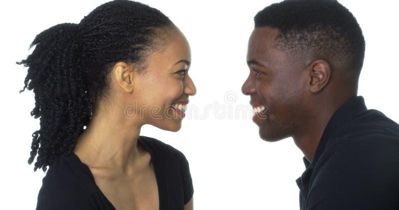 看彼此的愉快的年轻黑夫妇微笑 免版税库存图片