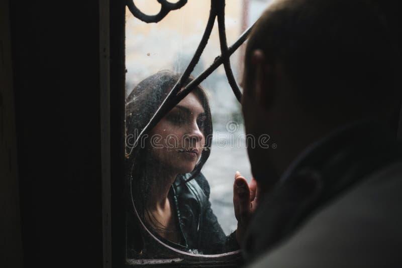 看彼此的欧洲年轻夫妇通过窗口 库存照片
