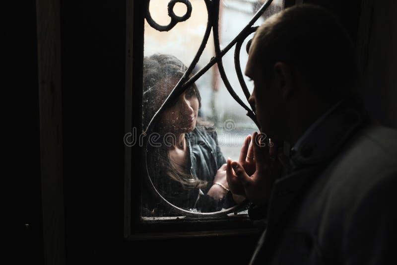 看彼此的欧洲年轻夫妇通过窗口 免版税图库摄影