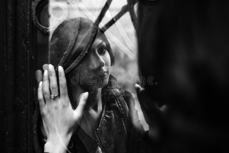 看彼此的欧洲年轻夫妇通过窗口 图库摄影