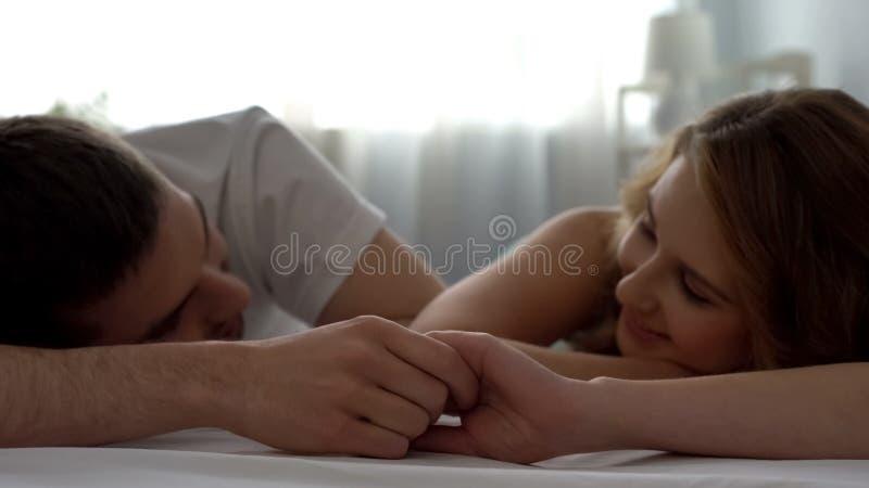 看彼此的甜夫妇充满爱,在床上握手,严紧 免版税库存照片