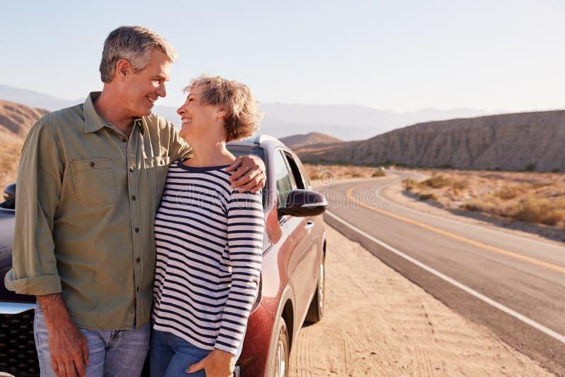 看彼此的资深夫妇立场在沙漠路旁 免版税库存图片