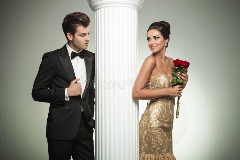 看彼此的年轻典雅的夫妇在专栏附近 免版税图库摄影