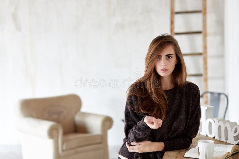 看往照相机和站立在屋子里的一地道和可爱的年轻女人的画象 库存图片