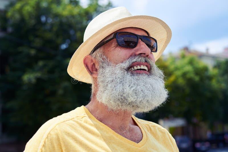 看往s的微笑的年长有胡子的人佩带的太阳镜 免版税库存照片