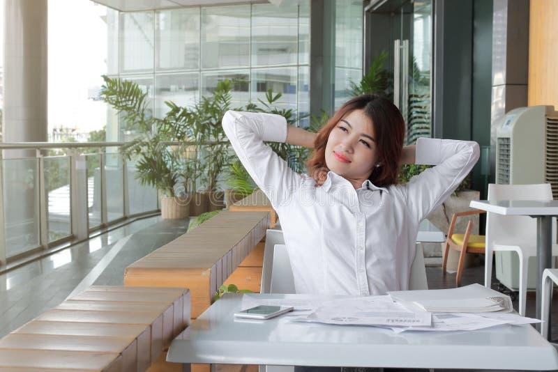 看很远办公室的轻松的年轻亚裔女商人画象  免版税库存图片