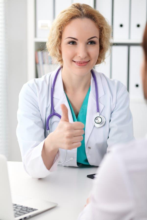 看患者的愉快的白肤金发的女性医生,当讲话与她和赞许时 医学、医疗保健和帮助concep 图库摄影