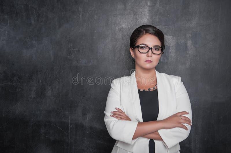 看您黑板的严肃的严密的老师 免版税库存图片