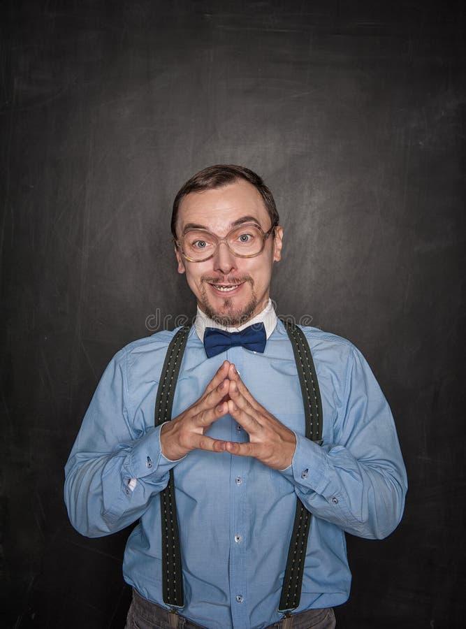 看您黑板的镜片的滑稽的老师 库存照片