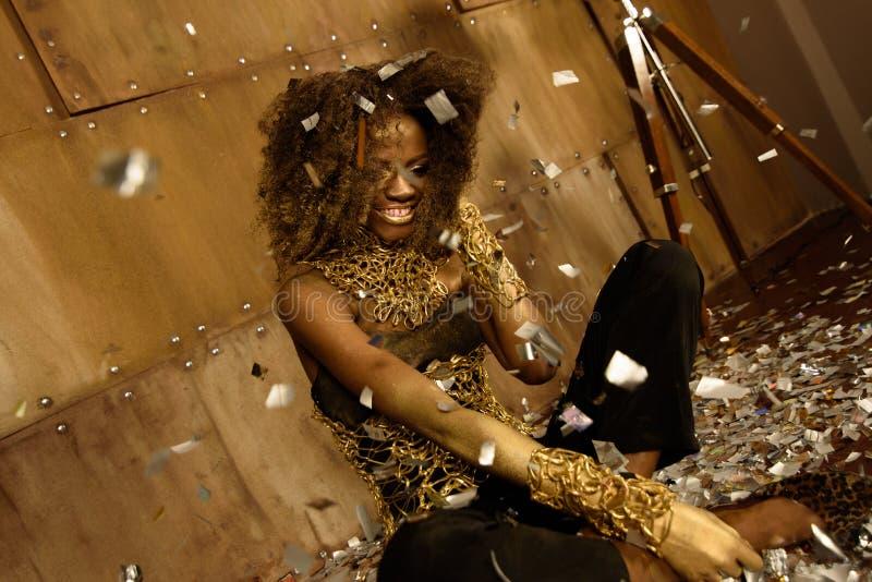 看惊奇在她的落的金五彩纸屑的愉快的黑人妇女,当下来坐地板时 库存图片