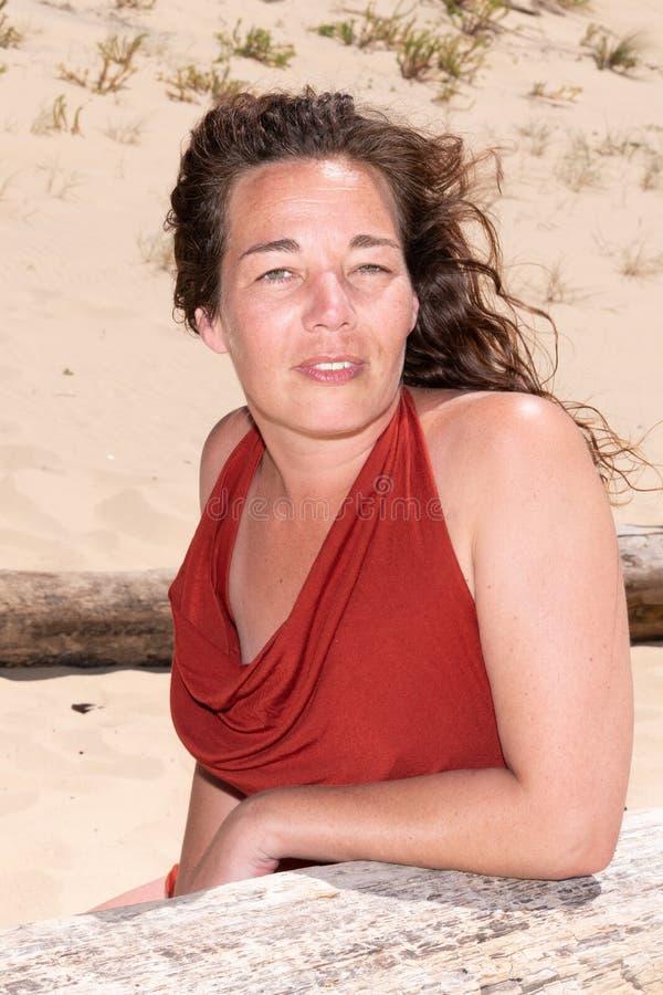 看愉快的中间年迈的妇女坐海滩和在旁边 免版税库存图片
