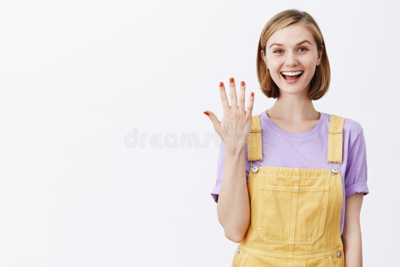 看我新的修指甲 有公平的短发的迷人的女性无忧无虑的妇女,显示与棕榈的第五和 库存照片