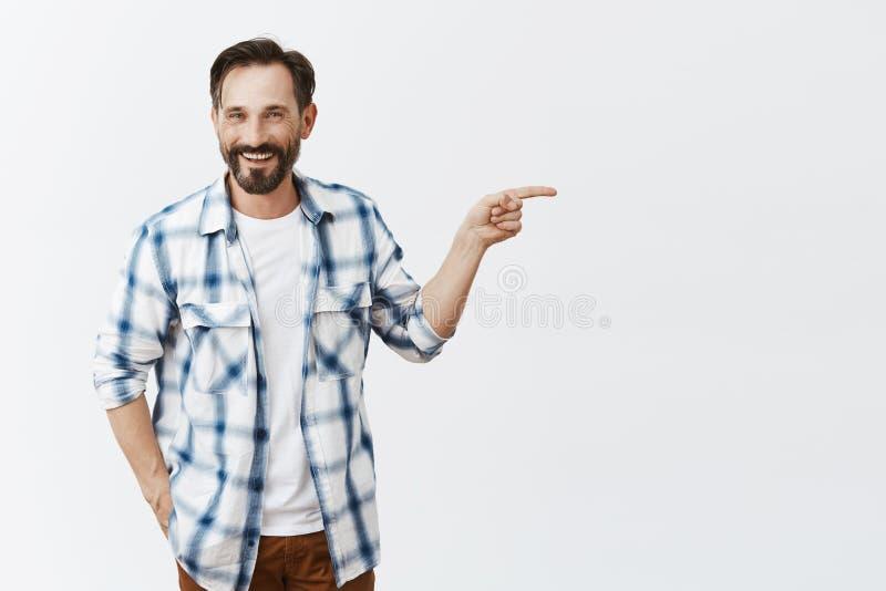 看我的孩子 有髭的迷人的愉快的父亲和胡子,握在口袋的手,站立在偶然轻松的姿势 免版税库存图片