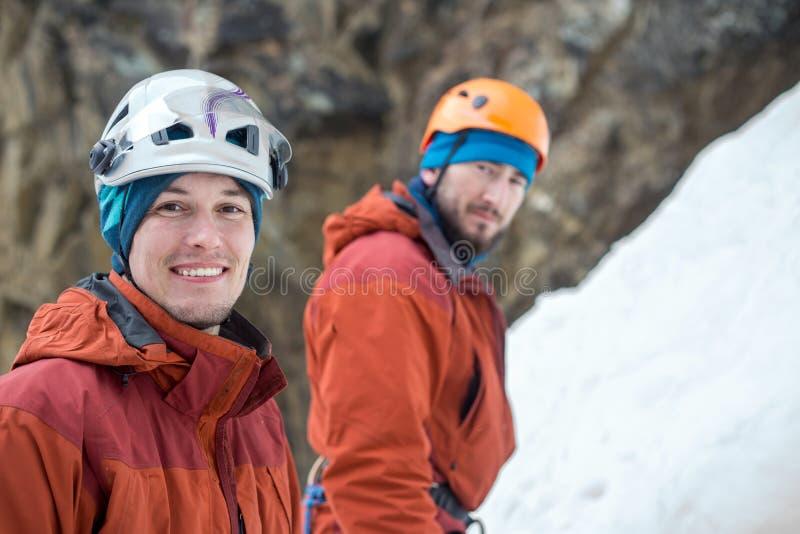 看我们的体育盔甲的两个年轻冰登山人在冰背景 免版税库存图片