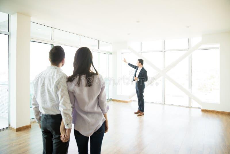 看房地产经纪商新的公寓的橱窗夫妇 免版税库存图片