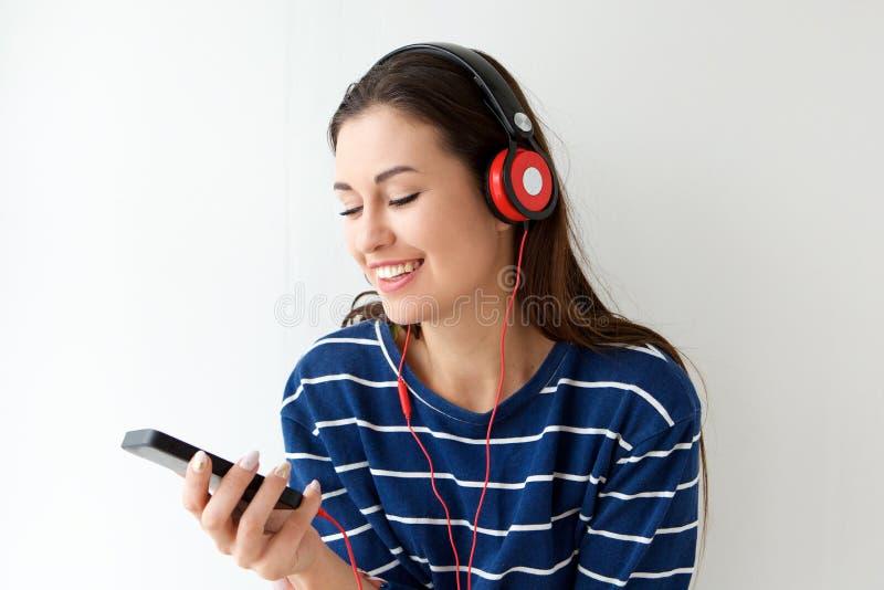 看手机和听到与耳机的音乐的愉快的少妇 免版税图库摄影