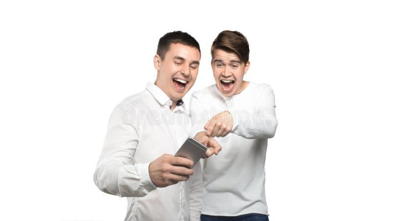 看手机和笑的两个人,被隔绝在白色背景 免版税库存照片
