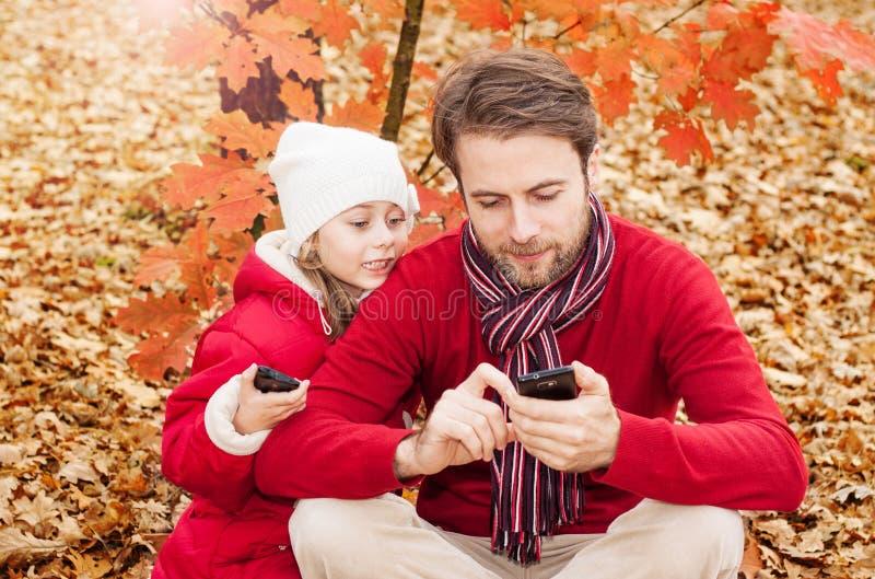 看手机在秋天的微笑的父亲和女儿停放 免版税图库摄影