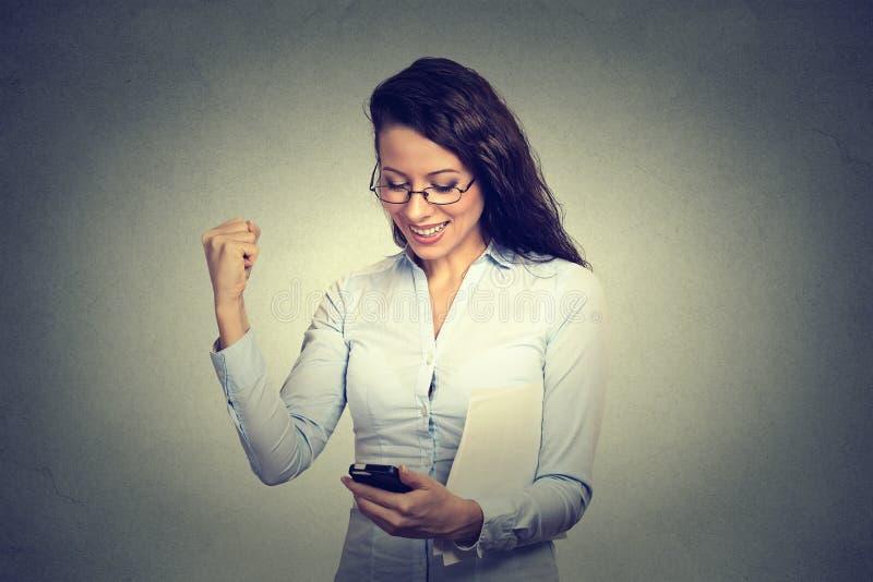 看手机微笑的抽的拳头的愉快的妇女庆祝成功 免版税库存图片