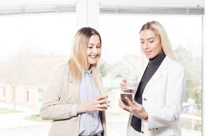 看手机的两个女性同事 免版税库存照片