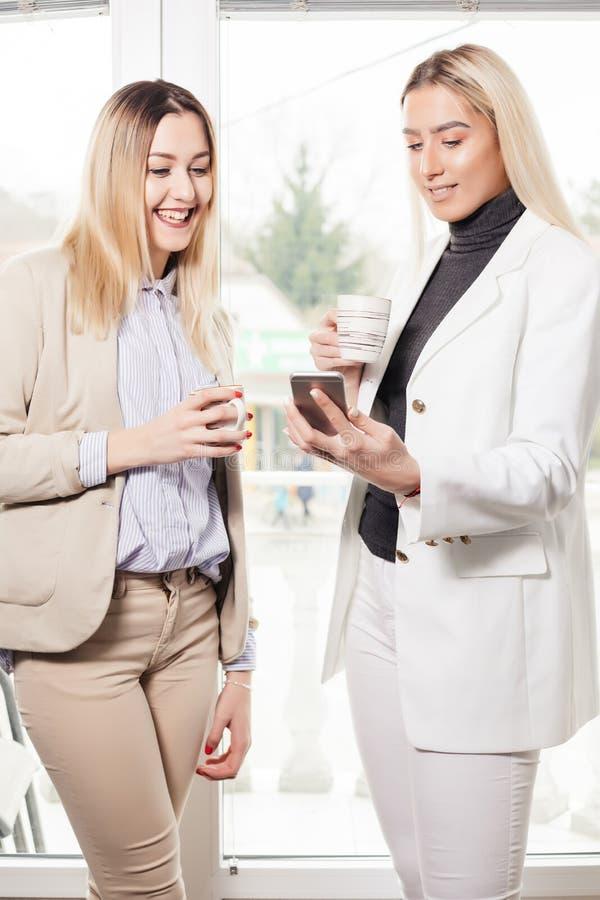 看手机的两个女性同事 库存照片