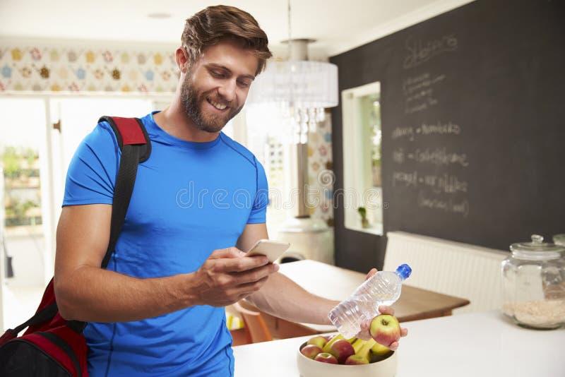 看手机的人佩带的健身房衣物 库存照片