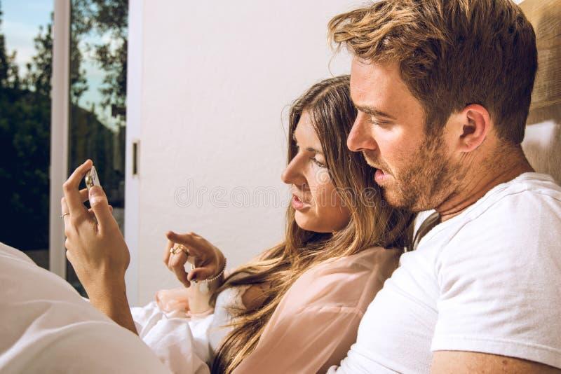 看手机的人和女孩` s年轻夫妇 看他们的手机的两三名男人和妇女特写镜头  库存照片