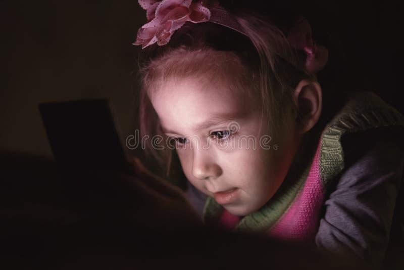 看手机的愉快的女孩 库存图片