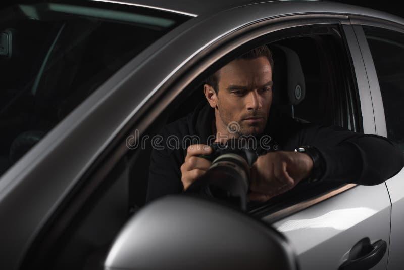 看手表和暗中侦察由与透镜的照相机的男性无固定职业的摄影师从他的 库存图片