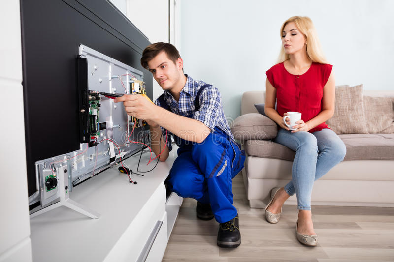 看技术员的妇女修理电视 图库摄影