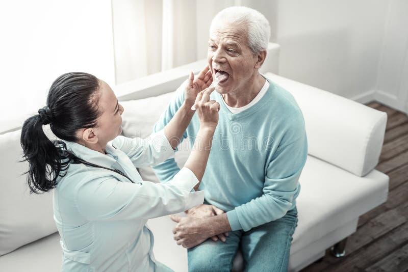 看护士的老严肃的人显示他的舌头 免版税库存图片