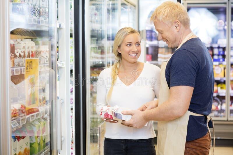 看推销员的微笑的顾客协助她在Supermarke 免版税库存照片
