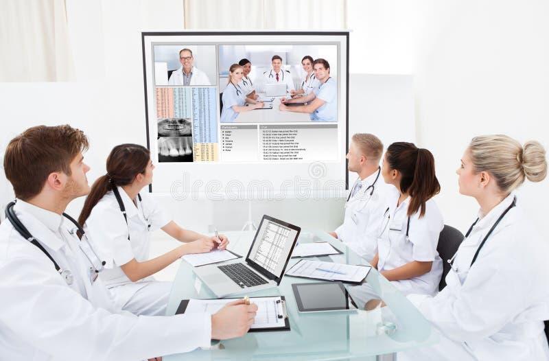 看放映机屏幕的医生队  库存图片