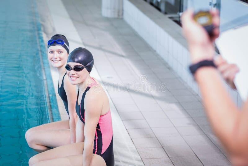 看教练员的微笑的游泳者 免版税库存照片