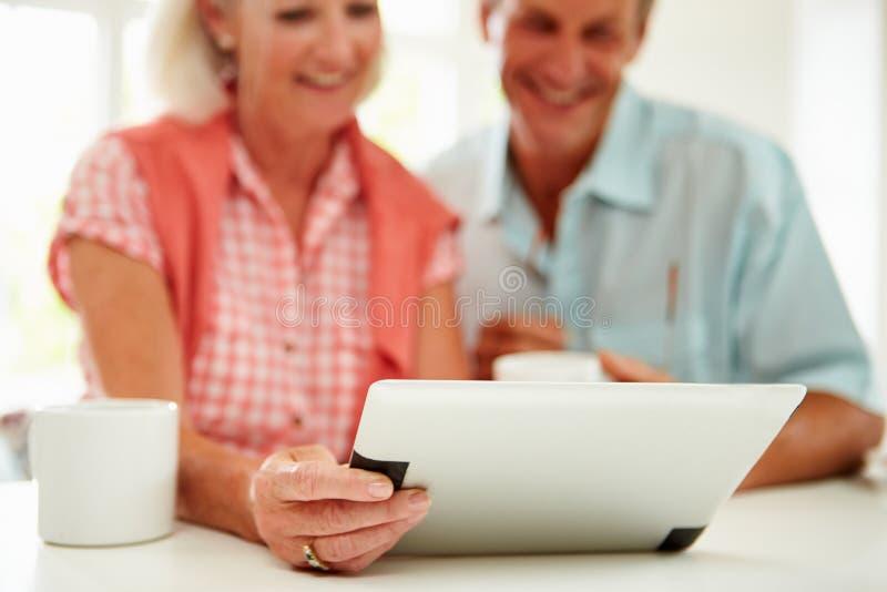 看数字式片剂的微笑的中世纪夫妇 免版税库存图片