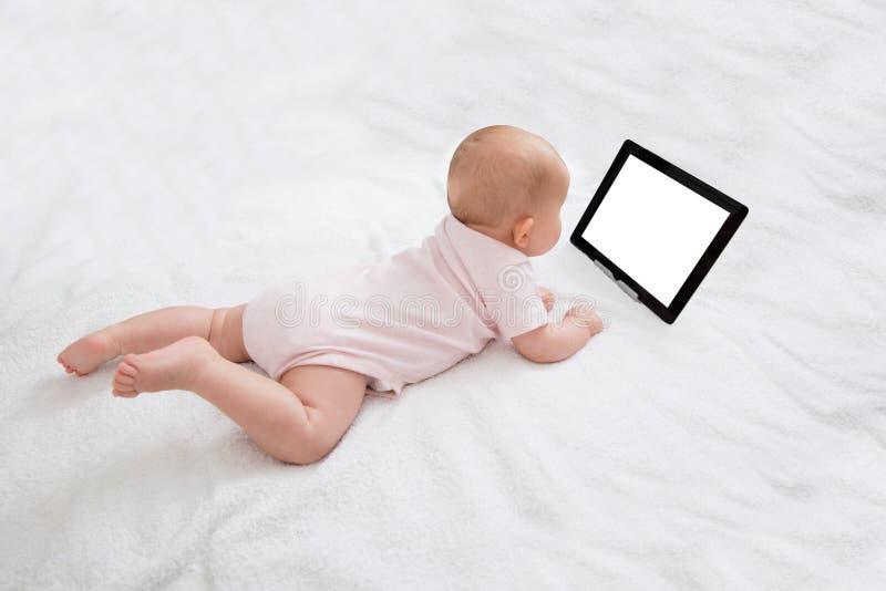 看数字式片剂的婴孩 免版税库存图片