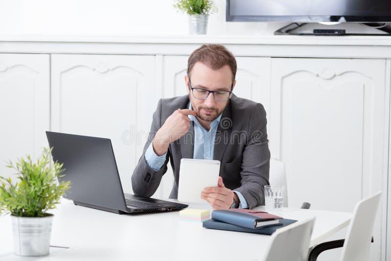 看数字式片剂设备的商人办公桌 库存照片