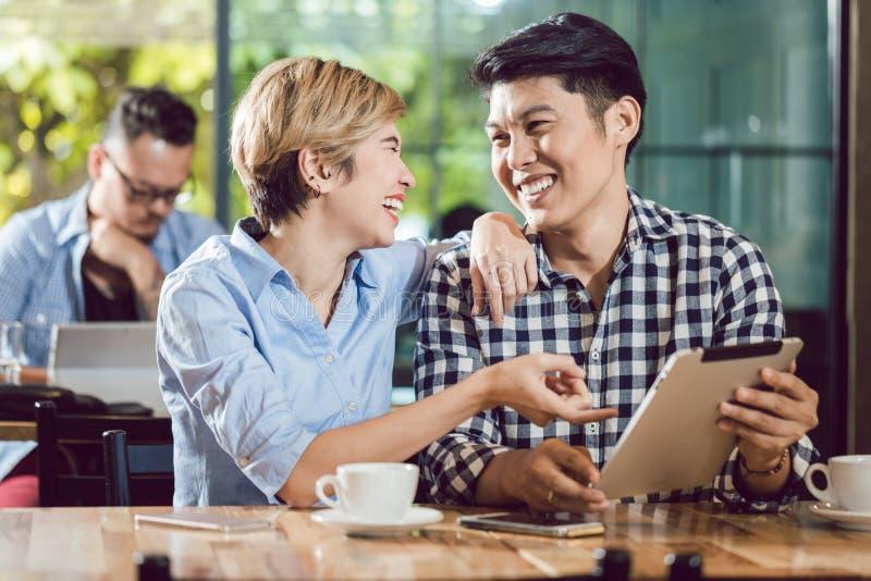 看数字片剂笑的夫妇 免版税库存照片