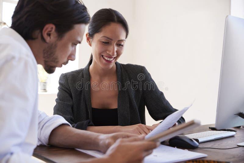 看文件在办公室,关闭的男人和妇女  免版税库存照片