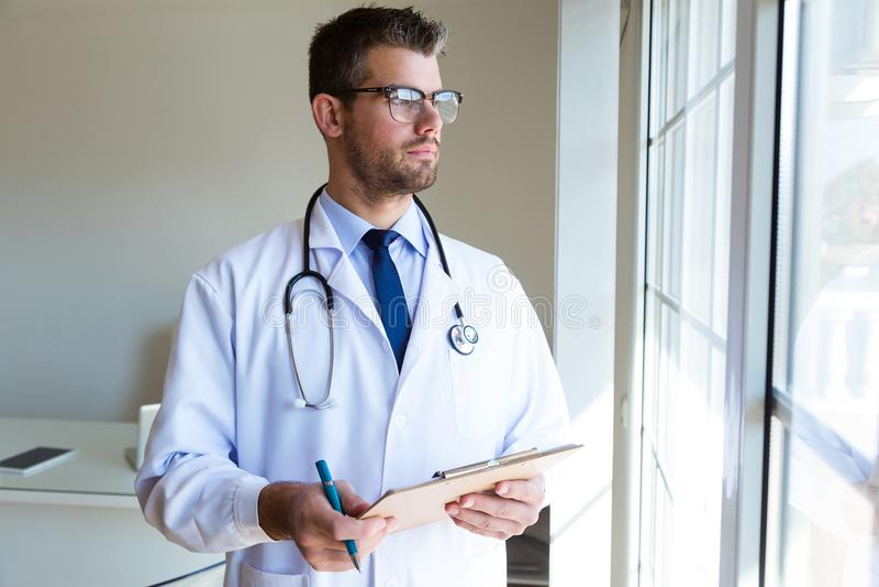 看斜向一边在办公室的确信的男性医生 免版税图库摄影