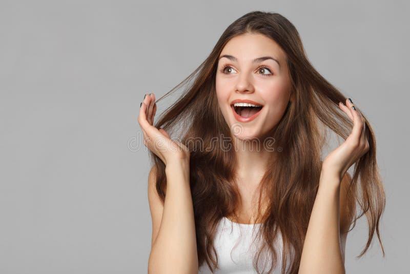 看斜向一边在兴奋的惊奇的愉快的美丽的妇女 查出在灰色背景 免版税图库摄影
