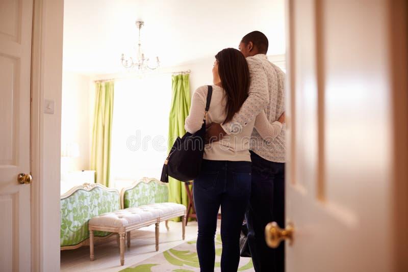 看旅馆客房,后面看法的年轻多种族夫妇 库存图片