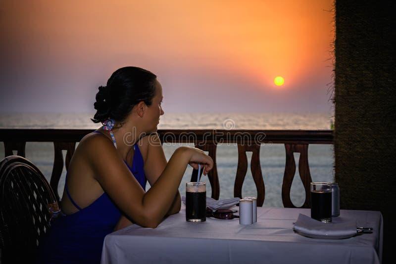 看日落的妇女在果阿 免版税库存照片